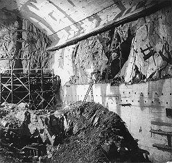 Hydro plant Lipno, Lipno I - Power plant, extraction of engine room core, on right concreted waste portal, in back front wall with problem zone, March 1957, historical photo