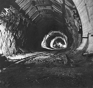 Hydro plant Lipno, waste tunnel, transport of digger D 500 into underground engine room, at ceiling of tunnel hangs timbering, February 1959, historical photo